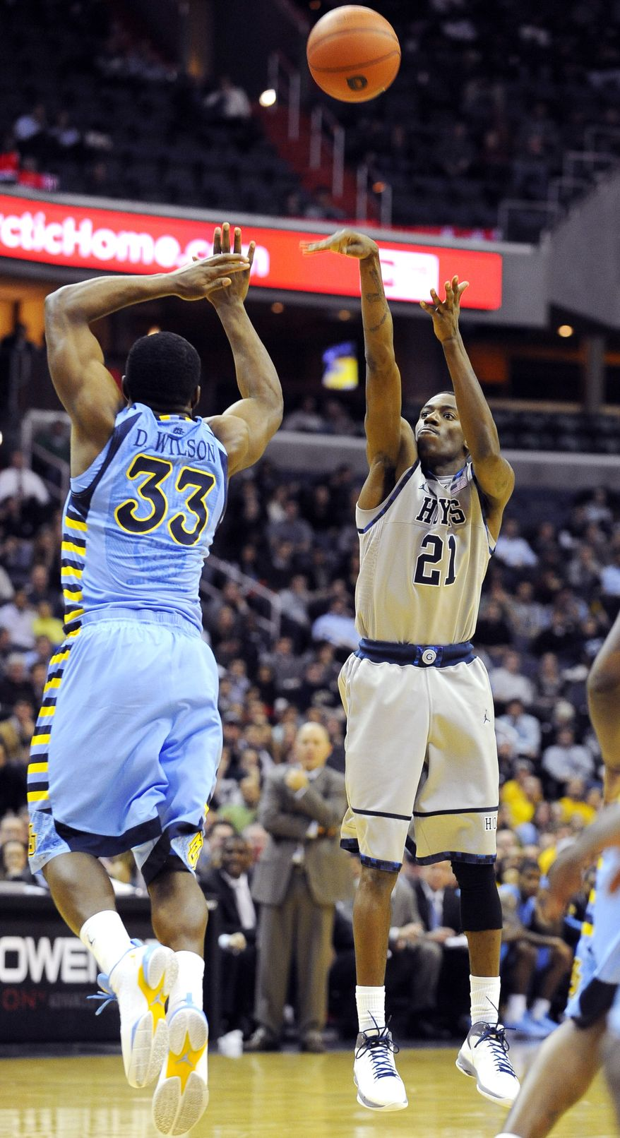 Georgetown guard Jason Clark shoots 3-pointer over Marquette's Derrick Wilson during the second half, Wednesday, Jan. 4, 2012, in Washington. Georgetown defeated Marquette 73-70. (AP Photo/Richard Lipski)