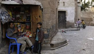 Yemeni vendor Hassan Azany (left), 19, sits Jan. 3, 2012, by his makeshift shop at an alley in the old city of Sanaa, Yemen. (Associated Press)