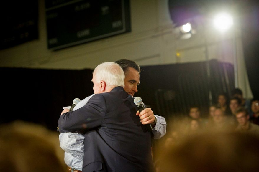 Former Massachusetts Gov. Mitt Romney (behind) and Sen. John McCain embrace in Manchester, N.H., on Wednesday, Jan. 4, 2012, as the Arizona senator endorses Mr. Romney's bid for the Republican presidential nomination. (Rod Lamkey Jr./The Washington Times)