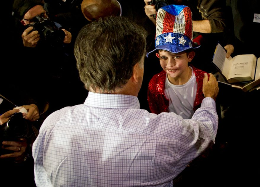 Former Massachusetts Gov. Mitt Romney greets a boy in the crowd in Manchester, N.H., on Wednesday, Jan. 4, 2012, as he leaves a town-hall-style campaign stop in his bid for the GOP presidential nomination. (Rod Lamkey Jr./The Washington Times)