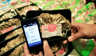 A smartphone shows amounts of radiation on a package of Maitake mushrooms for sale in Tokyo. A small but growing number of Internet-savvy moms in Japan, including Mizuho Nakayama (below), have turned into activists in search of answers about the March nuclear disaster. (Associated Press)
