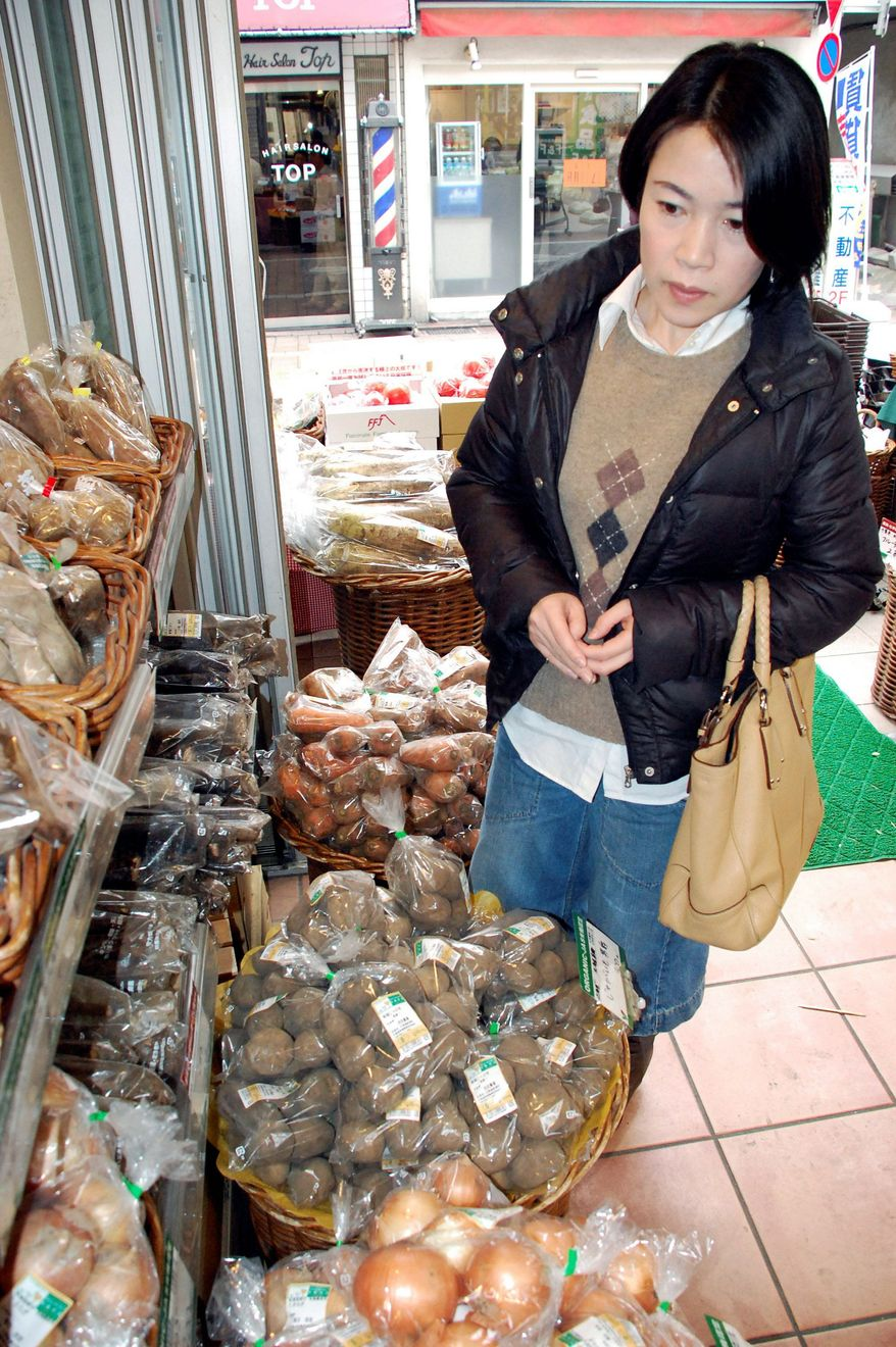 In this Thursday, Dec. 22, 2011 photo, Mizuho Nakayama shops at a grocery shop near her house in Tokyo. Japan's nuclear crisis has turned Nakayama into one of a small but growing number of Internet-savvy activist moms. In the days and weeks following the March 11 tsunami, frustration over the sketchy information coming from the government about the Fukushima Dai-ichi nuclear plant drove many Japanese to Twitter and alternative media webcasts. (AP Photo/Malcolm J. Foster)