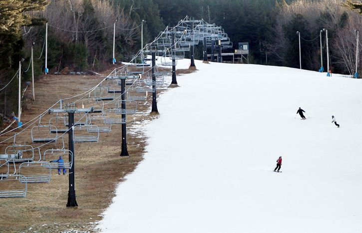Man-made snow coats a ski slope, but barren ground remains Thursday under a chairlift at Shawnee Peak ski resort in Bridgton, Maine. A dearth of snow in many regions nationwide is costing various businesses millions of dollars. (Associated Press)