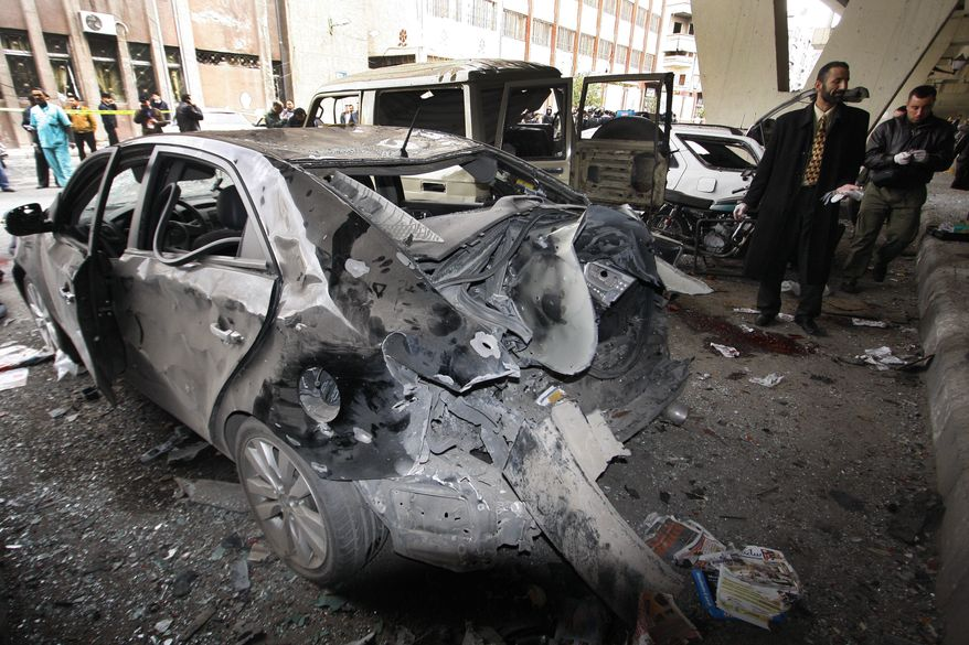 Syrian investigators inspect next to a damaged car at the scene of a bomb in Midan neighborhood of Damascus, Syria, on Jan. 6, 2012. An explosion ripped through a police bus, killing many in an attack authorities blamed on a suicide bomber, an official and state-run TV said. (Associated Press)