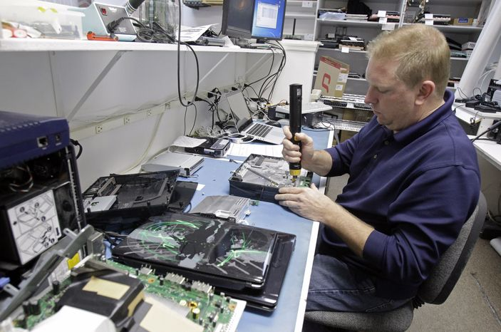 Technician Shawn Cable repairs a video game console Jan. 5, 2012, at the Laptops Plus computer store in Winter Park, Fla. (Associated Press)