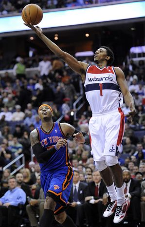 Washington Wizards guard Nick Young goes to the basket against New York Knicks forward Carmelo Anthony during the second half Friday, Jan. 6, 2012, in Washington. Anthony led all scorers with 37 points, while Young led the Wizards with 24. The Knicks won 99-96. (AP Photo/Nick Wass)