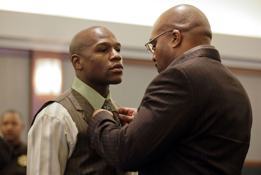 **FILE** Boxer Floyd Mayweather Jr. (left) has his tie adjusted by his manager Leonard Ellerbe on Dec. 21, 2011, while waiting for sentencing in Clark County District Court in Las Vegas. Mayweather was sentenced to 90 days in jail after pleading guilty to reduced battery domestic violence and harassment charges. (Associated Press)