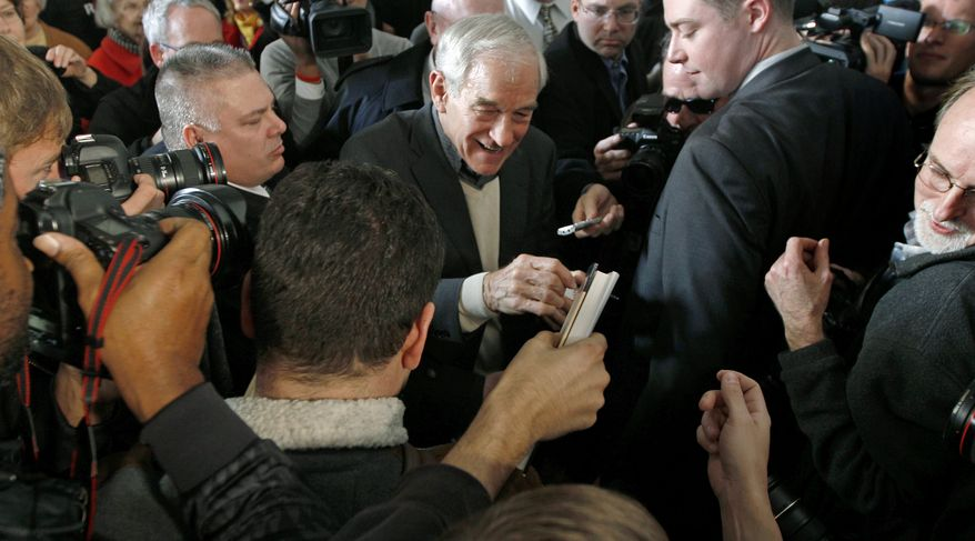 Republican presidential candidate Rep. Ron Paul, Texas Republican, smiles as he signs autographs Jan. 6, 2012, during a campaign rally in Nashua, N.H. (Associated Press)