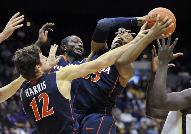Virginia forward Akil Mitchell (25) finds the going tough while pulling in a rebound with his teammates Joe Harris (12) and Assane Sene, background, during the second half against LSU on Monday, Jan. 2, 2012, in Baton Rouge, La. Virginia won 57-52. (AP Photo/Bill Feig)