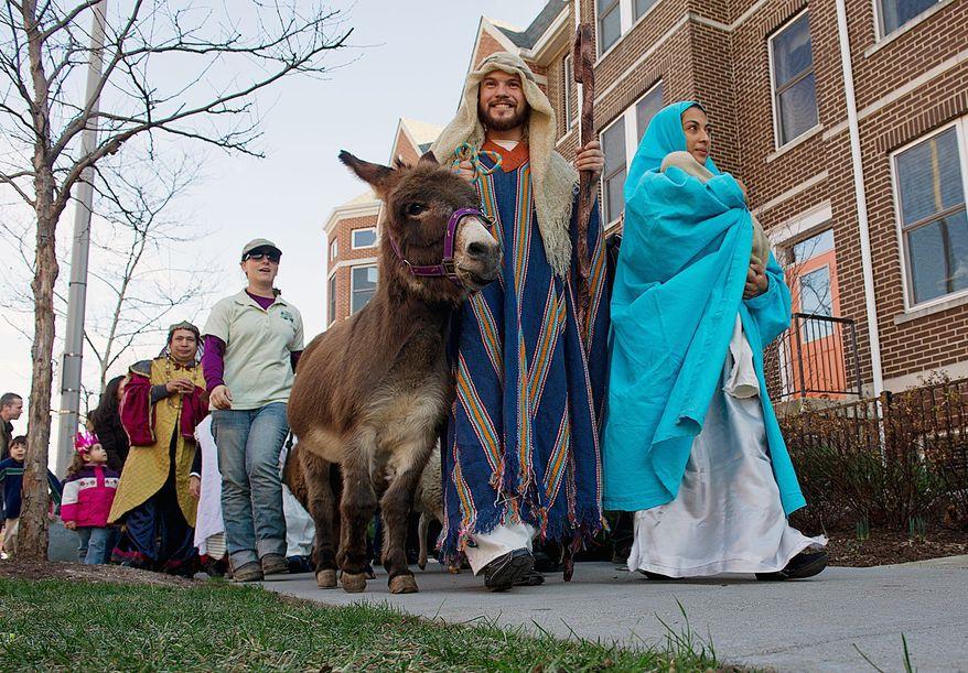 Manuel Sanchez and Rosmery Solorzano, playing Joseph and Mary, lead a Three Kings Day procession Sunday around the GALA Hispanic Theatre in Northwest. (Barbara L. Salisbury/The Washington Times)