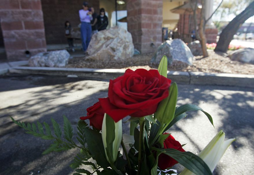 People gaze at a small memorial plaque on a rock at a Safeway supermarket on Saturday, Jan. 7, 2012, that commemorates the victims of the mass shooting on Jan. 8, 2011, in Tucson, Ariz. (AP Photo/Arizona Daily Star, Rick Wiley)