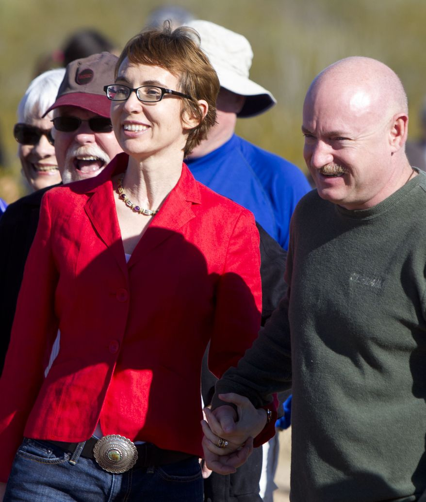 Rep. Gabrielle Giffords and her husband, retired Navy Capt. Mark Kelly, walk on the Davidson Canyon Gabe Zimmerman Memorial Trailhead on Saturday, Jan. 7, 2012, to pay tribute to Zimmerman, who was killed a year ago during the Tucson shooting. Zimmerman was the director of community outreach for Mrs. Giffords. (AP Photo/The Arizona Republic, Cheryl Evans)