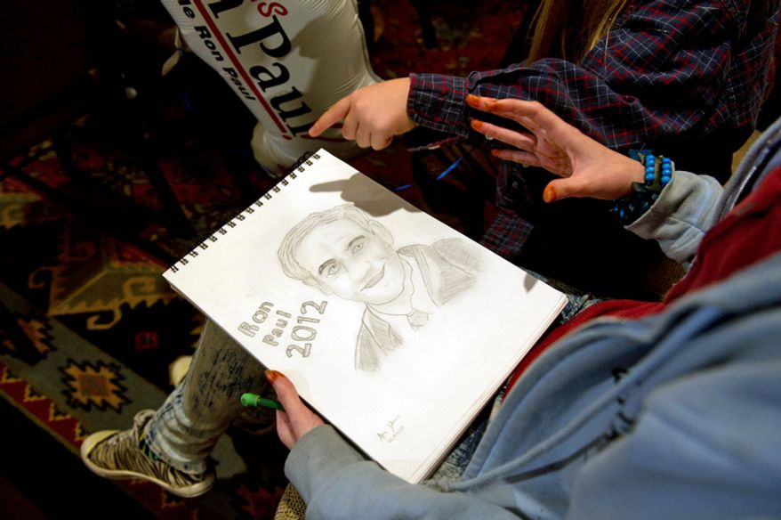 Allie Dennis, 16, of Meredith, N.H., holds a drawing she made of Republican presidential candidate Ron Paul, as she and others wait for his arrival for a town hall meeting. (Rod Lamkey Jr/ The Washington Times)
