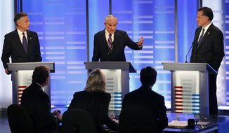 Former Utah Gov. Jon Huntsman, left, and former Massachusetts Gov. Mitt Romney, right, listen to Rep. Ron Paul, R-Texas, answer a question during a Republican presidential candidate debate at Saint Anselm College in Manchester, N.H., Saturday, Jan. 7, 2012. (AP Photo/Elise Amendola)