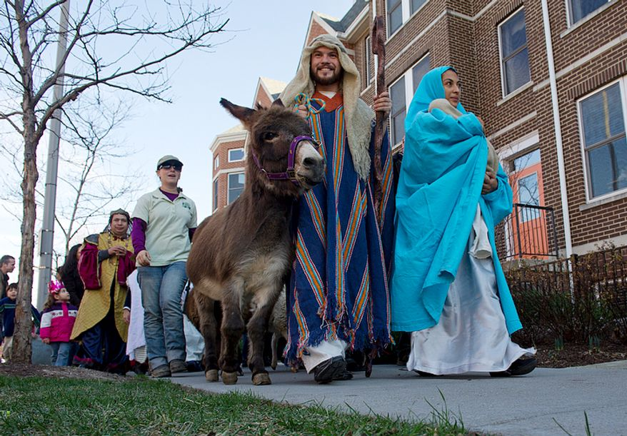 Manuel Sanchez, left, and Rosmery Solorzano, playing Joseph and Mary, lead a procession in Columbia Heights on Sunday, Jan. 8, 2012 as part of a big Three Kings Day celebration to honor Epiphany, the day that the three wise men arrived in Bethlehem. (Barbara L. Salisbury/The Washington Times)