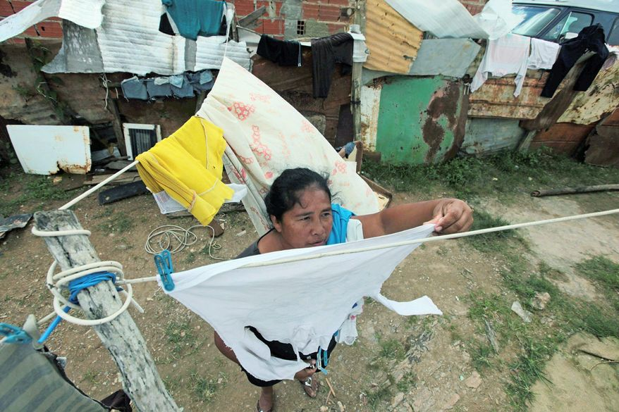 Yolanda Silva hangs clothes to dry outside her home made of corrugated zinc in Winche on the outskirts of Caracas, Venezuela. (Associated Press)