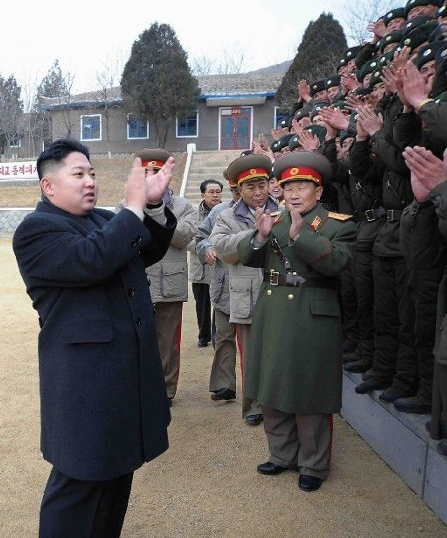FILE - In this Jan. 1, 2012 file photo released by the Korean Central News Agency and distributed Monday, Jan. 2, 2012 in Tokyo by the Korea News Service, North Korea's new leader Kim Jong Un, left, applauds with military personnel as he inspects Seoul Ryu Kyong Su 105 Guards Tank Division of the Korean People's Army at an undisclosed location in North Korea to congratulate servicepersons on New Year's day. Kim Jong Un's first inspection visit without his father Kim Jong Il was a well-documented New Year's Day trip to the tank unit with symbolic ties to his family and his nation's history. (AP Photo/Korean Central News Agency via Korea News Service, File) JAPAN OUT UNTIL 14 DAYS AFTER THE DAY OF TRANSMISSION