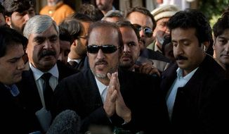 Senator and lawyer Babar Awan (center) discusses the Pakistani Supreme Court's warning Tuesday that it could dismiss the prime minister if he doesn't obey the court's 2009 demand that criminal cases against the president be reopened. (Associated Press)