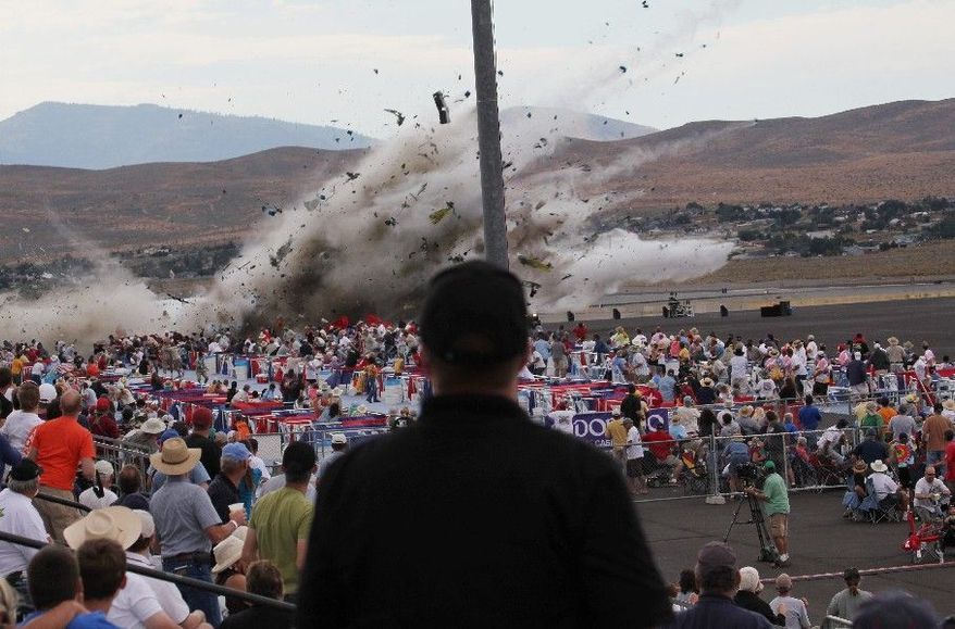 ** FILE ** Hollywood stunt pilot Jimmy Leeward's souped-up World War II-era fighter plane, a P-51 Mustang, crashes into the edge of the grandstands, sending shrapnel into the crowd, at the Reno Air Show in Reno, Nev., in September. Eleven people died and about 70 more were badly injured. (Associated Press)