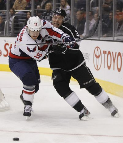 Washington Capitals center Jeff Halpern battles Los Angeles Kings defenseman Jack Johnson for the puck during the first period in Los Angeles on Monday, Jan. 9, 2012. (AP Photo/Chris Carlson)
