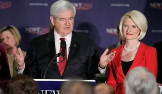 Republican presidential candidate, former House Speaker Newt Gingrich speaks to supporters at his rally headquarters Tuesday, Jan. 10, 2012, in Manchester, N.H., as his wife Callista watches. (AP Photo/Jim Cole)