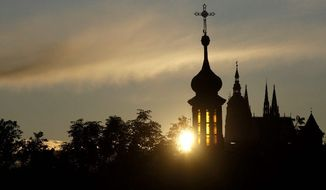 The sun sets behind St. Vitus Cathedral in Prague in 2009. The Czech Republic's coalition government has OK'd a plan to compensate religious organizations for property seized by the former Czechoslovakia's communist regime. (Associated Press)
