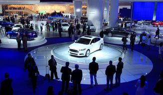 A 2013 Ford Fusion is showcased at the North American International Auto Show in Detroit. The annual exposition opens to the public Saturday after charity and press previews. Last year, the Detroit auto show brought in about $350 million in business. The show creates temporary but nonetheless welcome jobs in a city with a high rate of unemployment. (Associated Press)