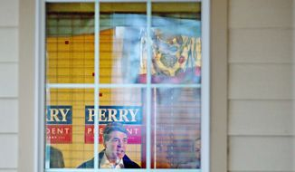Texas Gov. Rick Perry is seen through a window as he delivers a stump speech during a campaign stop at Lizard's Thicket restaurant in Lexington, S.C., on Wednesday. (Associated Press)