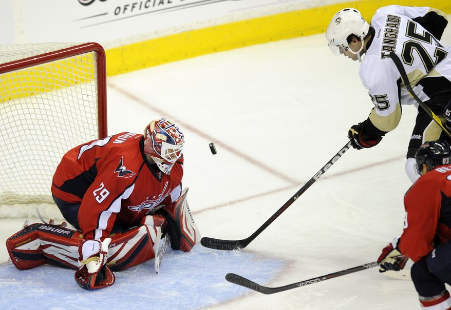 Washington Capitals goalie Tomas Vokoun (29) keeps his eye on the puck against Pittsburgh Penguins left wing Eric Tangradi (25) during the second period of an NHL game, Wednesday, Jan. 11, 2012, in Washington. (AP Photo/Nick Wass)