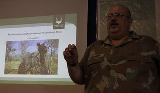 **FILE** Army Brig. Gen. Koos Liebenberg stands July 19, 2011, in front of a projected slide of soldier with a poached rhino during a presentation at Kruger National Park in South Africa to visiting press on border patrol and rhino poaching. (Associated Press)