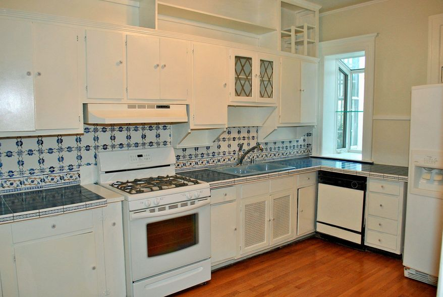 The kitchen has hardwood flooring and a greenhouse window.