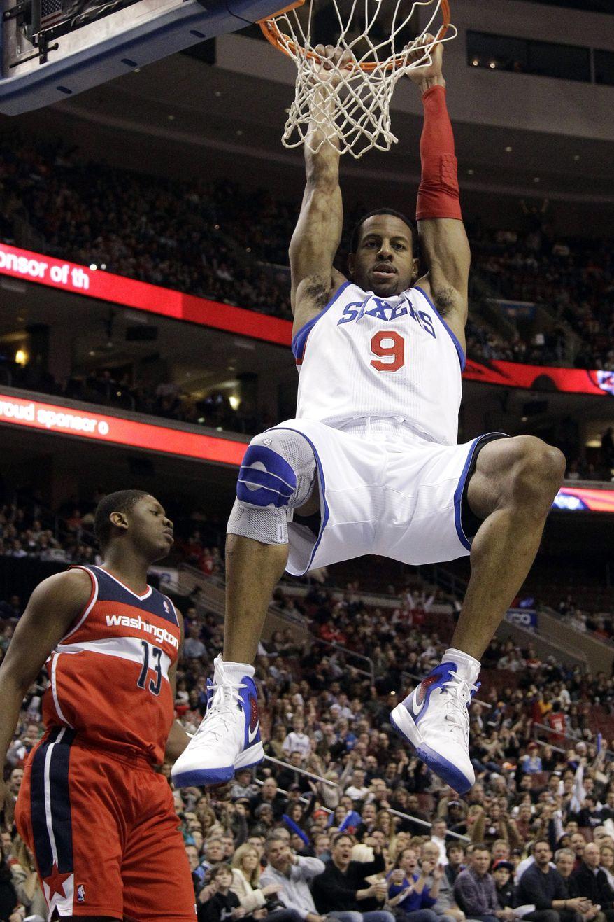 Philadelphia 76ers' Andre Iguodala hangs on the rim after dunking against Washington Wizards' Kevin Seraphin in the second half, Friday, Jan. 13, 2012, in Philadelphia. Philadelphia won 120-89. (AP Photo/Matt Slocum)