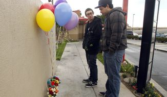 Dillon Ruiz, left, and Chris Juarez of Anaheim pay their respects at a makeshift memorial site where a homeless man was killed Friday night outside a fast-food restaurant in Anaheim, Calif., Saturday, Jan. 14, 2012. Police arrested a suspect in connection with the death. The death follows reports of the earlier stabbing deaths of three homeless men in north Orange County since Dec. 21. Police suspect all three were victims of a serial killer. It was not known if the latest death was connected to the other killings. (AP Photo/Alex Gallardo)