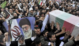 Beside a poster of Iranian supreme leader Ayatollah Ali Khamenei, mourners carry a flag draped coffin of Mostafa Ahmadi Roshan, a chemistry expert and a director of the Natanz uranium enrichment facility in central Iran, in his funeral ceremony, on Friday, Jan. 13, 2012, in Tehran, Iran. (AP Photo/Iranian Students News Agency, Mehdi Ghasemi)