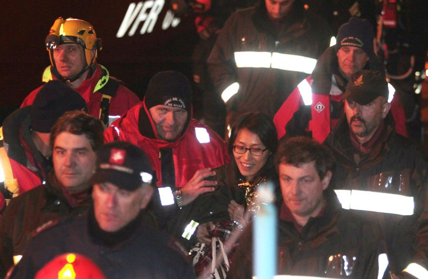 A passenger from South Korea, center, walks with Italian Firefighters after being rescued from the luxury cruise ship Costa Concordia which ran aground the tiny Tuscan island of Giglio, Italy, Sunday, Jan. 15, 2012. The luxury cruise ship ran aground off the coast of Tuscany, sending water pouring in through a 160-foot (50-meter) gash in the hull and forcing the evacuation of some 4,200 people from the listing vessel early Saturday, the Italian coast guard said. (AP Photo/Gregorio Borgia)