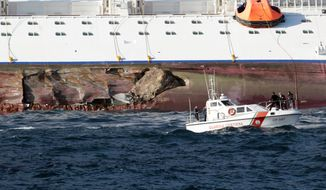Rocks emerge from the damaged side of a luxury cruise ship Costa Concordia that run aground the tiny Tuscan island of Giglio, Italy, Saturday, Jan. 14, 2012. (AP Photo/Gregorio Borgia)