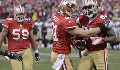 San Francisco 49ers tight end Vernon Davis celebrates with tight end Justin Peelle and guard Jonathan Goodwin after scoring on a 14-yard touchdown pass from quarterback Alex Smith against the New Orleans Saints during the fourth quarter Saturday, Jan. 14, 2012, in San Francisco. (AP Photo/Paul Sakuma)
