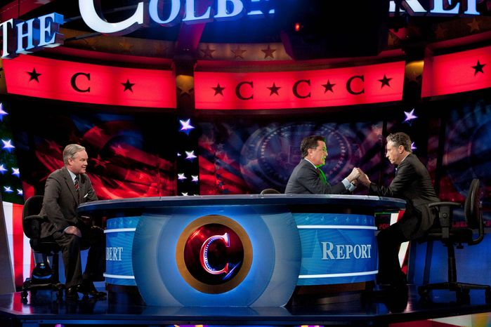 """Stephen Colbert signs over his super PAC to Comedy Central cohort Jon Stewart on """"The Colbert Report"""" on Thursday as lawyer Trevor Potter looks on. Mr. Colbert is contemplating a run for president in South Carolina. (Comedy Central via Associated Press)"""