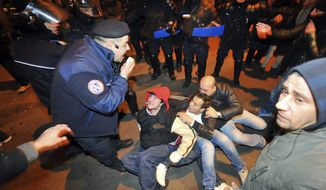 Protesters sit on the ground surrounded by Romanian police in University Square, the scene of the first anti-communist protest in 1989, in Bucharest, Romania. (Associated Press)