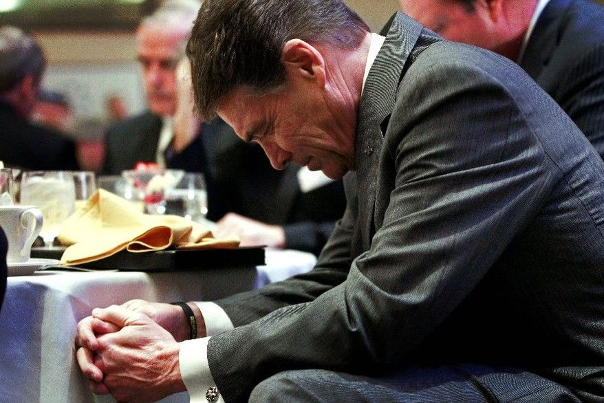Republican presidential hopeful Rick Perry bows his head in prayer at a Faith and Freedom Coalition prayer breakfast in Myrtle Beach, S.C., on Sunday. No state is more under siege by the federal government than South Carolina, and the Texas governor is arguably the GOP field's best advocate for states' rights. (Associated Press)