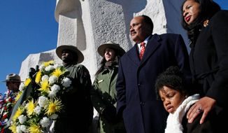 Martin Luther King III (third from right), the son of civil rights leader Martin Luther King Jr., stands Sunday with his wife, Arndrea, and daughter, Yolanda, before the memorial dedicated to his father on the Mall in Washington. Americans are honoring Martin Luther King Jr. on Monday, 83 years after his birth. (Associated Press)