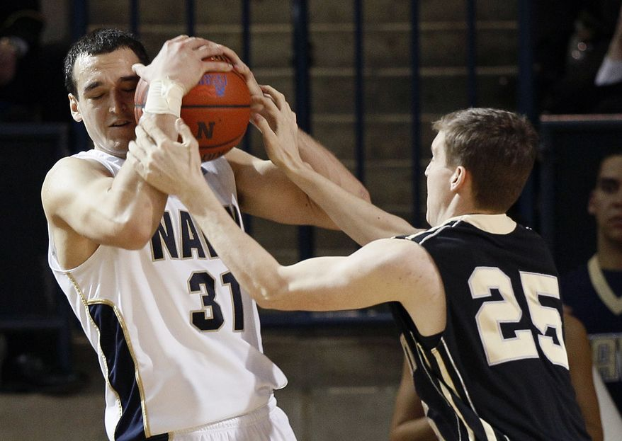 Navy forward J.J. Avila tries to keep the ball away from Army forward Whit Thornton in the second half in Annapolis, Md., Saturday, Jan. 14, 2012. Army won 75-62, despite a game-high 21 points from Avila. (AP Photo/Patrick Semansky)