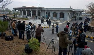 Pakistani media gather Monday in Islamabad, where a hearing of a judicial commission is in session. The Supreme Court set up the panel to investigate a secret-memo scandal in response to a petition filed by a group of opposition politicians. Prime Minister Yusuf Raza Gilani must appear Thursday to explain his refusal to cooperate in the probe. (Associated Press)