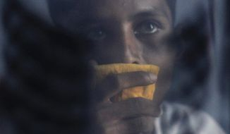 """Mohammed Shamim Sheikh, who suffers from multi-drug-resistant tuberculosis, is seen Jan. 16, 2012, through an x-ray of his chest as he listens to a social worker at his home in a slum on the outskirts of Mumbai, India. Indian doctors have reported the country's first cases of """"totally drug-resistant tuberculosis,"""" a long-feared and virtually untreatable form of the killer lung disease. (Associated Press)"""