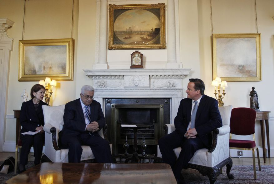 British Prime Minister David Cameron (right) speaks with Palestinian Authority President Mahmoud Abbas during their meeting at 10 Downing Street in London on Monday, Jan. 16, 2012. The woman at left is unidentified. (AP Photo/Lefteris Pitarakis, Pool)