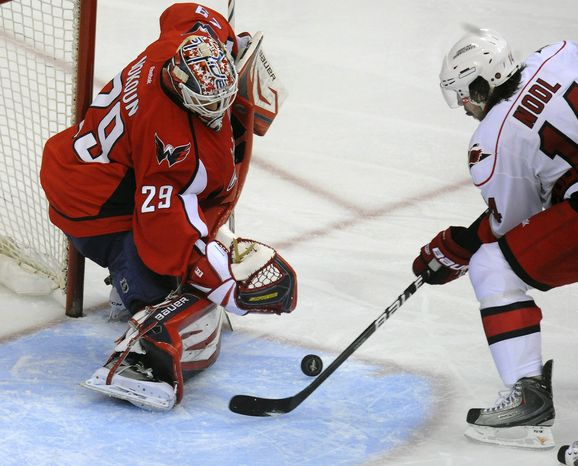 Washington Capitals' goalie Tomas Vokoun (29) blocks a shot by Carolina Hurricanes' Andreas Nodl during the second period of their NHL game, Sunday, Jan. 15, 2012, in Washington. The Capitals defeated the Hurricanes 2-1. (AP Photo/Richard Lipski)