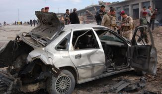 Iraqi security forces inspect the scene of a car-bomb attack outside Mosul, Iraq, 225 miles northwest of Baghdad, on Monday, Jan. 16, 2012. (AP Photo)