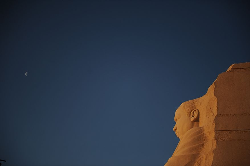 The moon is seen in the sky above the Martin Luther King Jr. Memorial on the National Mall in Washington on Monday, Jan. 16, 2012. (Rod Lamkey Jr./The Washington Times)