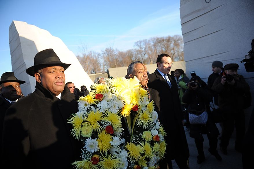 The Rev. Al Sharpton (center) carries a wreath with Harry E. Johnson (left), president and CEO of the Washington, D.C., Martin Luther King Jr. National Memorial Project Foundation Inc., and Washington Mayor Vincent C. Gray (right) during the foundation's wreath-laying ceremony at the foot of the Stone of Hope at the Martin Luther King Jr. Memorial on the National Mall in Washington on Monday, Jan. 16, 2012. (Rod Lamkey Jr./The Washington Times)
