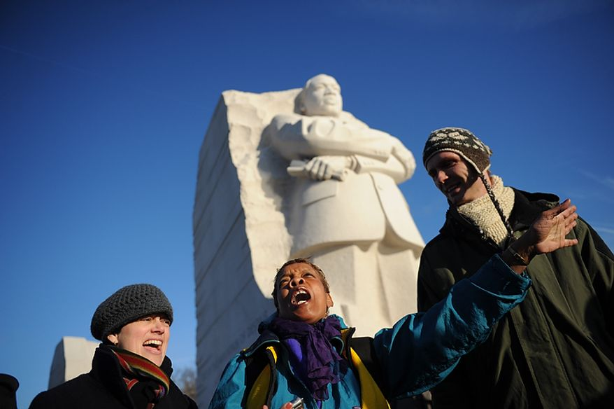 Beverly Steed (center) of Washington joins others in song under the shadow of the Martin Luther King Jr. Memorial on the National Mall in Washington on Monday, Jan. 16, 2012. (Rod Lamkey Jr./The Washington Times)